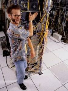 Man standing by cables in computer room